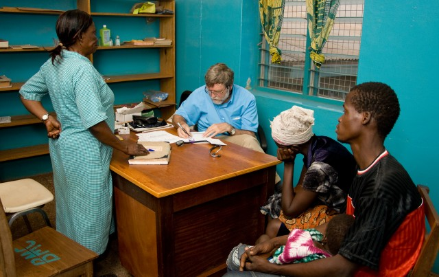 Volunteer Dr. Alan Web examines a patient on clinic day at BMC